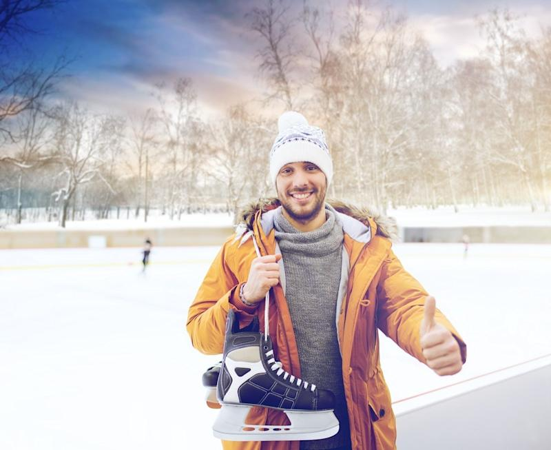man with ice-skates showing thumbs up on skating rink