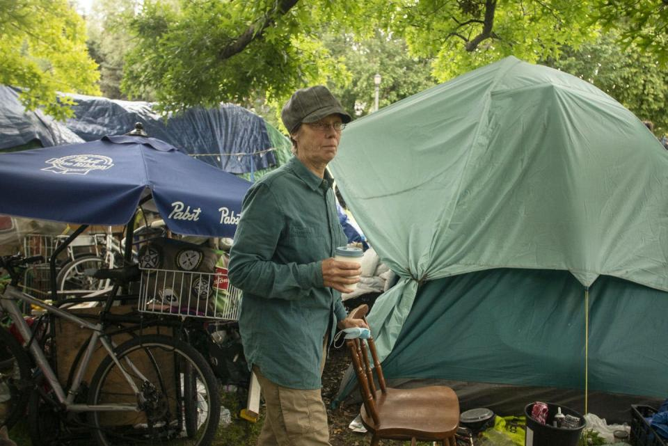"""<span class=""""caption"""">A woman prepares to pack her belongings during an eviction process at a homeless encampment in Toronto last June.</span> <span class=""""attribution""""><span class=""""source"""">THE CANADIAN PRESS/Chris Young </span></span>"""