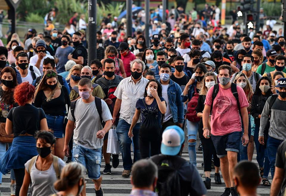 People wearing protective face masks walk by the Brazil Avenue, near the Constitucion train station, in Buenos Aires, on April 6, 2021. - Covid-19 infections in the last 24 hours in Argentina rose to 20,870, a record since the beginning of the coronavirus pandemic, the Ministry of Health reported on Tuesday, April 6. (Photo by RONALDO SCHEMIDT / AFP) (Photo by RONALDO SCHEMIDT/AFP via Getty Images)