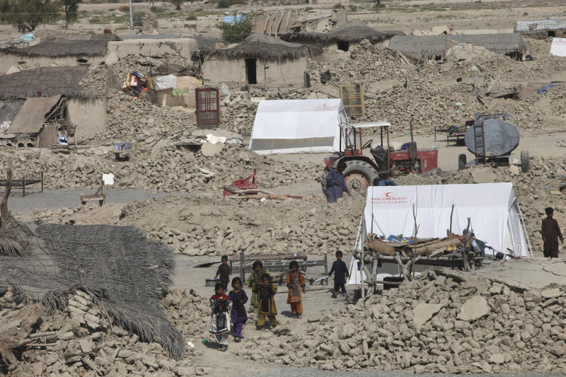 Pakistani children walk amid the rubble of houses, which were destroyed in Tuesday's earthquake, in the remote district of Awaran in Baluchistan province, Pakistan, Friday, Sept. 27, 2013. Desperate Pakistani villagers in remote areas hit by the massive earthquake this week said they are still waiting for government aid to reach them. (AP Photo/Shakil Adil)