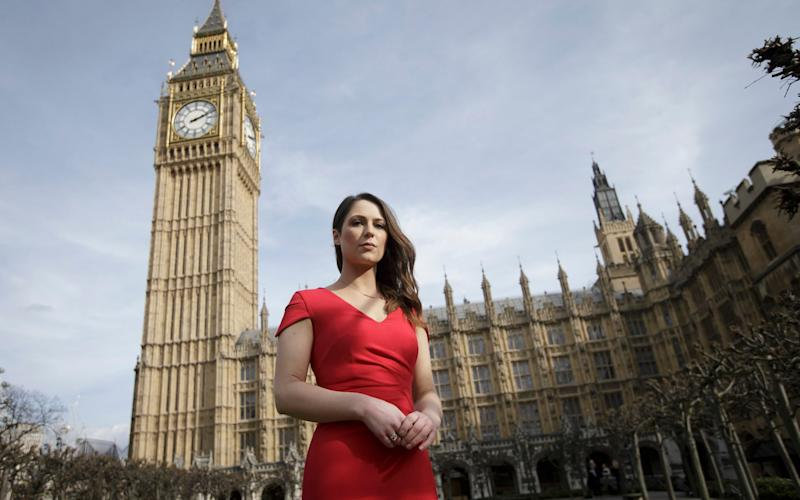 The lead campaigner for a high heels ban Nicola Thorp stands outside the Houses of Parliament - AP