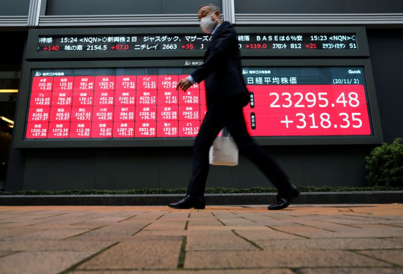 A man wearing a protective face mask walks past a stock quotation board outside a brokerage, amid the coronavirus disease (COVID-19) outbreak, in Tokyo