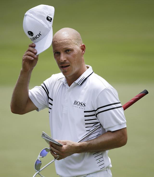 Ben Crane leaves the 18th green after finishing his second round of the St. Jude Classic golf tournament Friday, June 6, 2014, in Memphis, Tenn. Crane finished the day at 12-under 128. (AP Photo/Mark Humphrey)