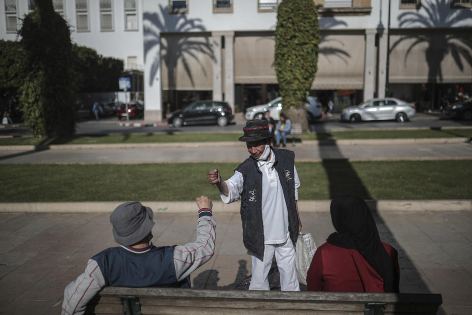 Belhussein Abdelsalam, 58, a Charlie Chaplin impersonator gives to a friend, on an avenue in Rabat, Morocco, Tuesday, March 23, 2021. When 58-year-old Moroccan Belhussein Abdelsalam was arrested and lost his job three decades ago, he saw Charlie Chaplin on television and in that moment decided upon a new career: impersonating the British actor and silent movie maker remembered for his Little Tramp character. (AP Photo/Mosa'ab Elshamy)