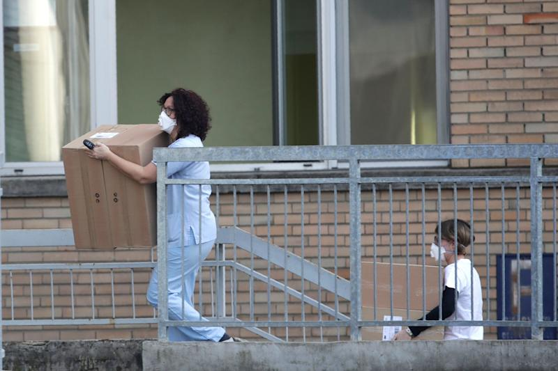 Hospital personnel carry boxes into the hospital of Codogno, near Lodi in Northern Italy, Friday, Feb. 21,2020. Health officials reported the country's first cases of contagion of COVID-19 in people who had not been in China. The hospital in Codogno is one of the hospitals - along with specialized Sacco Hospital in Milan - which is hosting the infected persons and the people that were in contact with them and are being isolated. (AP Photo/Luca Bruno) (Photo: ASSOCIATED PRESS)