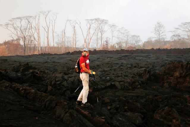 <p>Mark Clawson, 64, attempts to walk to his home on the outskirts of Pahoa during ongoing eruptions of the Kilauea Volcano in Hawaii, June 6, 2018. (Photo: Terray Sylvester/Reuters) </p>