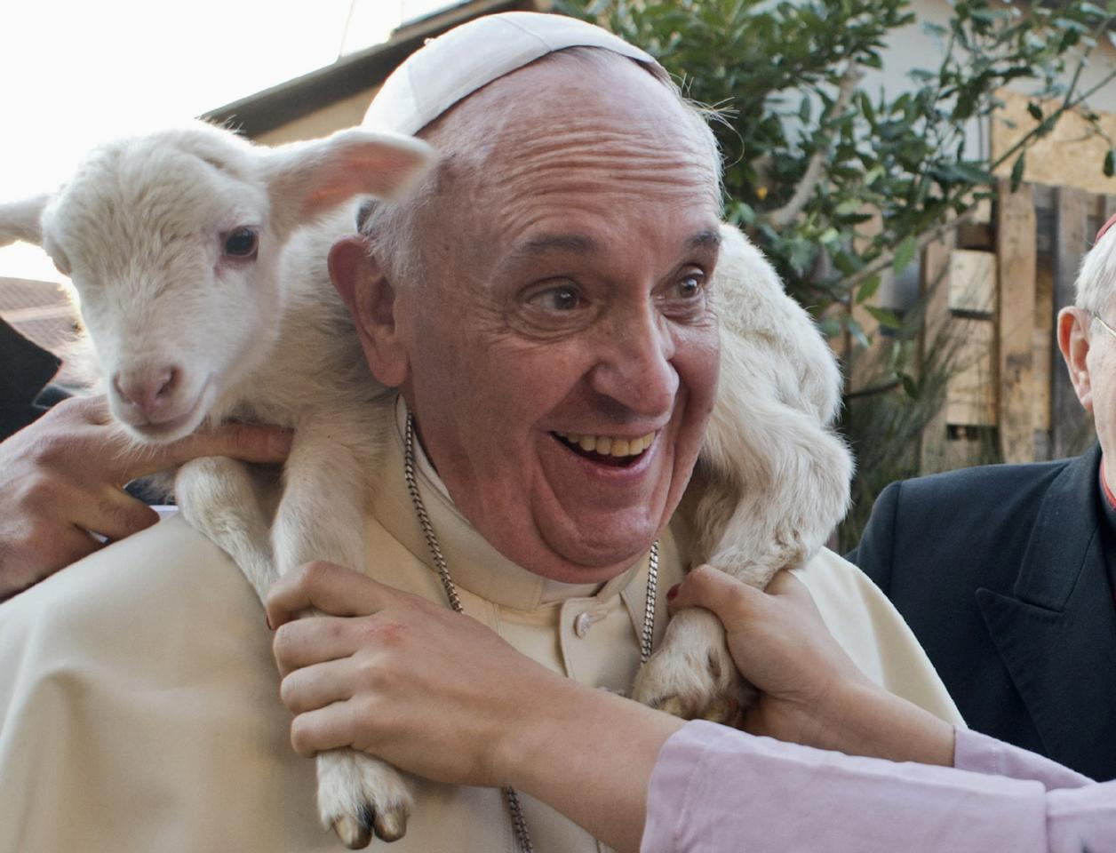 A woman dressed as a character from the nativity scene puts a lamb around the neck of Pope Francis as he arrives to visit the Church of St Alfonso Maria dei Liguori in the outskirts of Rome