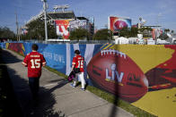 FILE - In this Feb. 4, 2021, file photo, Kansas City Chiefs fans walk past Raymond James Stadium ahead of Super Bowl 55 in Tampa, Fla. The city is hosting Sunday's Super Bowl football game between the Tampa Bay Buccaneers and the Kansas City Chiefs. (AP Photo/Charlie Riedel, File)
