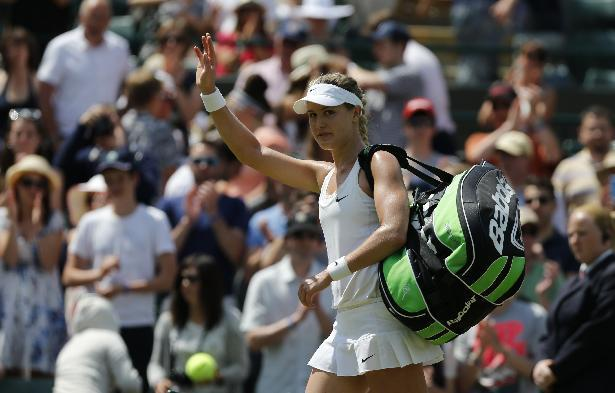 Eugenie Bouchard of Canada waves as she walks off court after defeating Angelique Kerber of Germany in their women's singles quarterfinal match at the All England Lawn Tennis Championships in Wimbledon, London, Wednesday, July 2, 2014. (AP Photo/Ben Curtis)