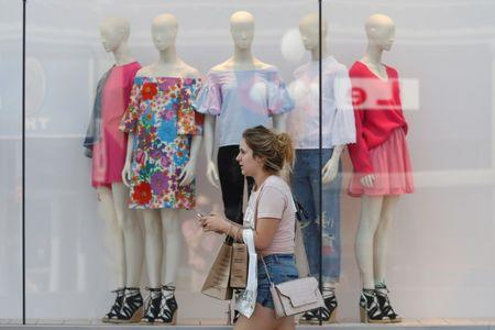 A woman carries shopping bags while walking past a window display outside a retail store in Ottawa