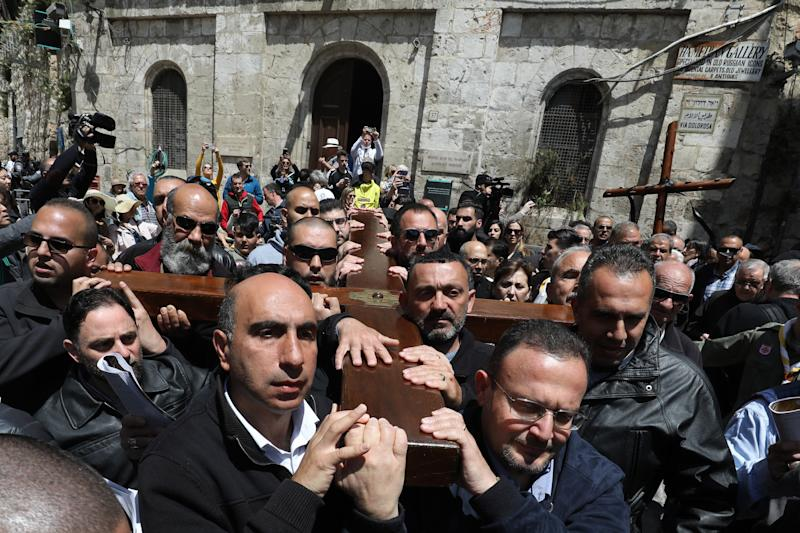 Members of a local Catholic Palestinian parish carry a wooden cross along the Via Dolorosa (Way of Suffering) in Jerusalem's Old City on Good Friday. (GALI TIBBON via Getty Images)