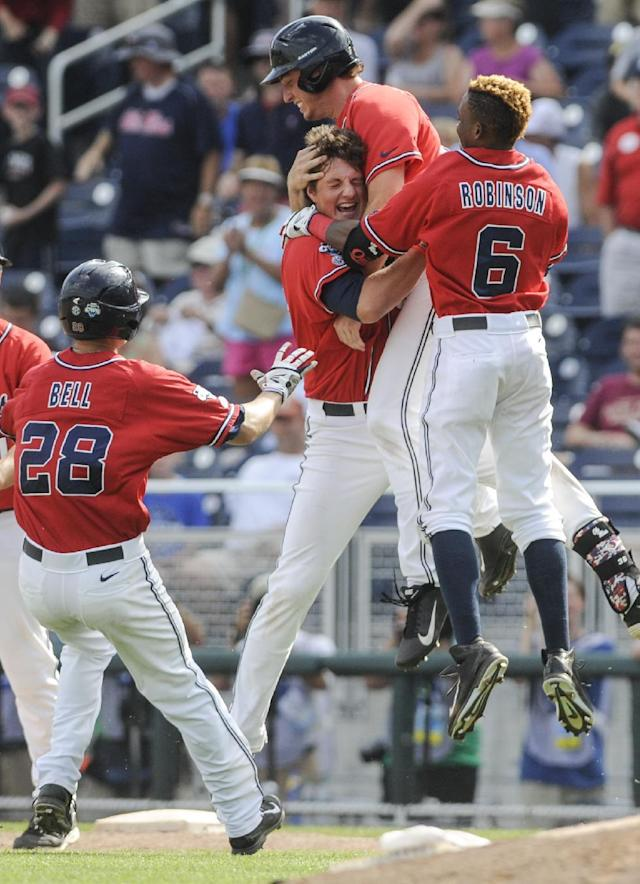 Mississippi players from left: Brantley Bell (28), John Gatlin, Aaron Greenwood and Errol Robinson celebrate their 2-1 win over Texas Tech in an NCAA baseball College World Series elimination game in Omaha, Neb., Tuesday, June 17, 2014. (AP Photo/Eric Francis)