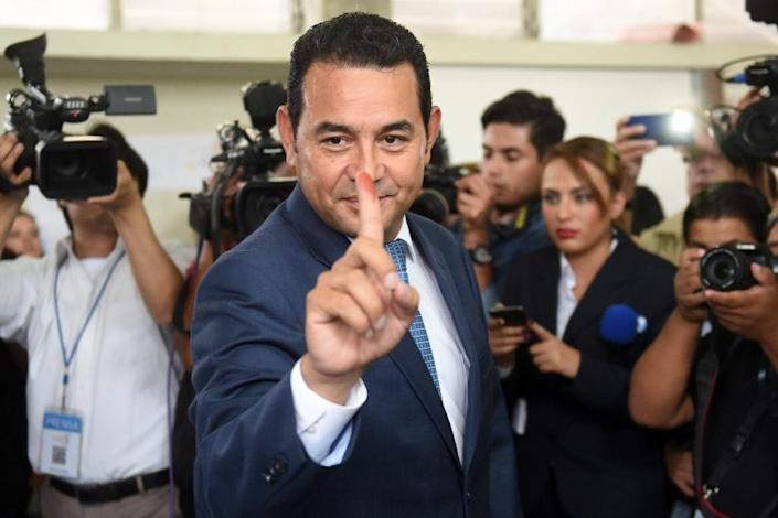 Guatemalan presidential candidate for the National Front of Convergence party, Jimmy Morales, shows his inked finger at a polling station in Mixco, during general elections on September 6, 2015 (AFP Photo/Marvin Recinos)