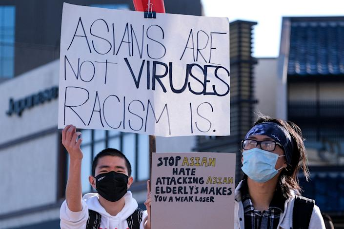 """Demonstrators wearing face masks and holding signs take part in the rally """"Love Our Communities: Build Collective Power"""" to raise awareness of anti-Asian violence at the Japanese American National Museum in Little Tokyo in Los Angeles in March. (Photo: RINGO CHIU via Getty Images)"""