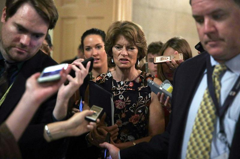 Sen. Lisa Murkowski is surrounded by members of the