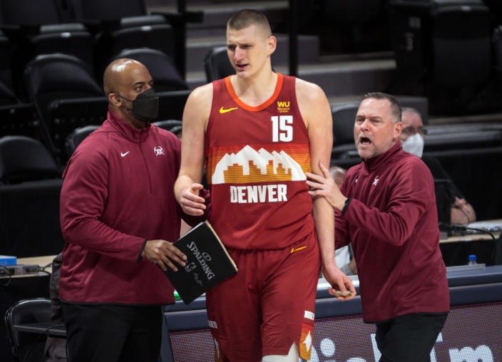 Denver Nuggets center Nikola Jokic (15) is led to the bench by Nuggets coach Michael Malone, right, and an unidentified assistant after Jokic was called for a technical foul against the Portland Trail Blazers in the third quarter of Game 2 of a first-round NBA basketball playoff series Monday, May 24, 2021, in Denver. (AP Photo/Joe Mahoney)