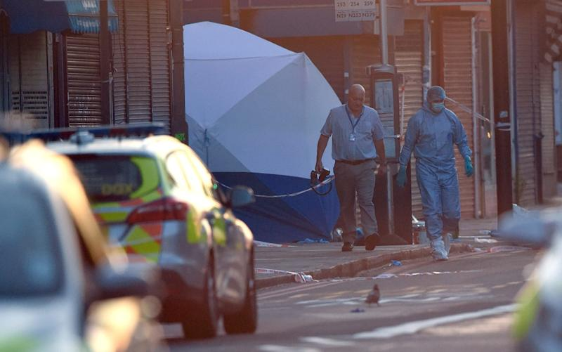 A police forensics officer walks from the scene - Credit: Carl Court/Getty
