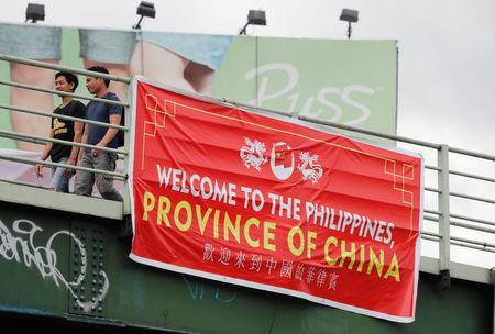 "Residents walk past a banner reading ""Welcome to the Philippines, Province of China"" on an overpass along the C5 road intersection in Taguig, Metro Manila, Philippines July 12, 2018. REUTERS/Erik De Castro"