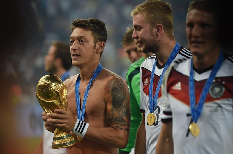 Ozil celebrates with the World Cup trophy after Germany's 2014 success over Argentina and long before the storm which has caused him to quit the national side (AFP Photo/Patrik STOLLARZ)