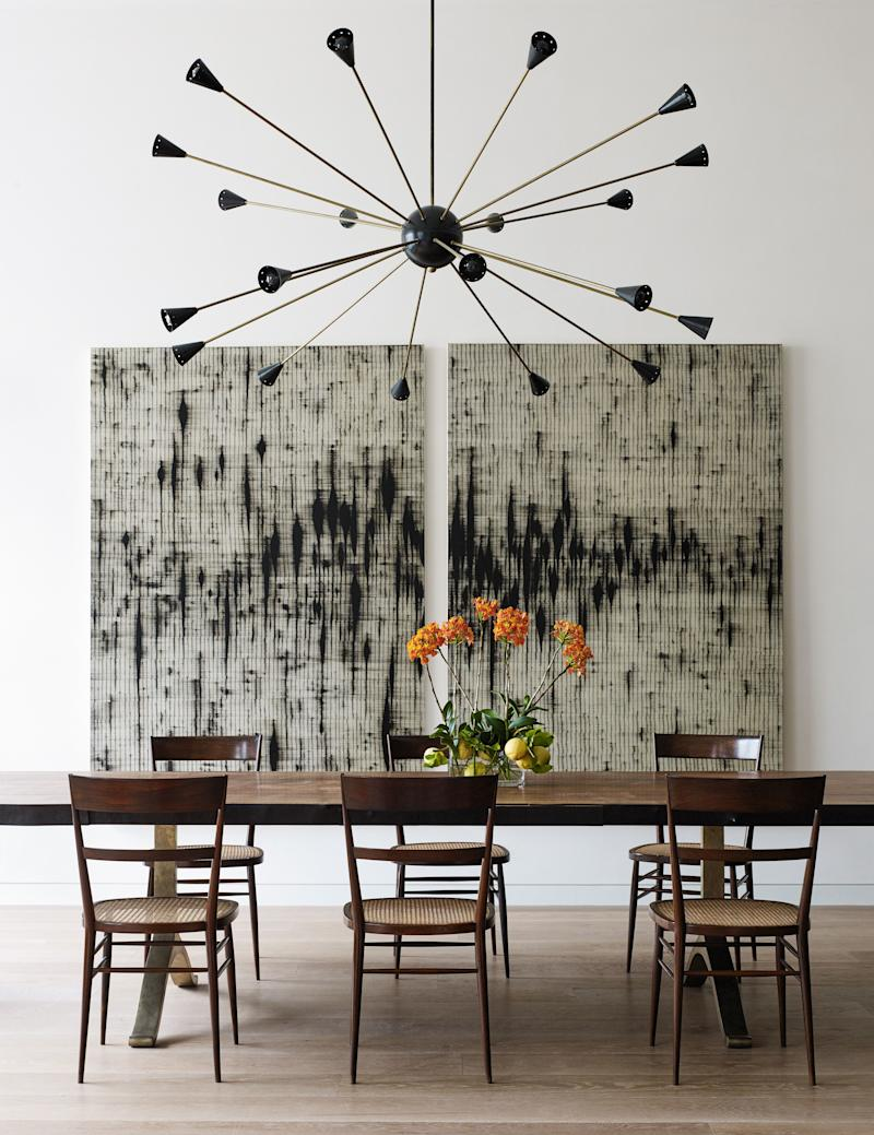 The dining table is by BDDW, and the chairs are by Joaquim Tenreiro, designed in Brazil in 1942 and purchased from R & Company. The voluminous ceiling height is purposely filled by a monumental Sputnik-style pendant from ma+39. The paintings are by Mark Francis.