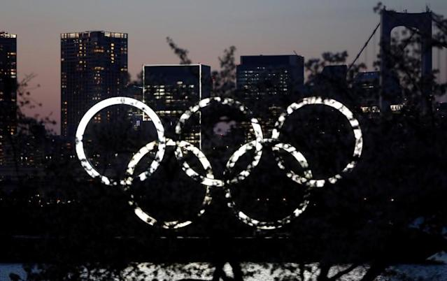 The giant Olympic rings are seen in the dusk through a tree at the waterfront area at Odaiba Marine Park after postponing Games due to the outbreak of coronavirus disease (COVID 19), in Tokyo