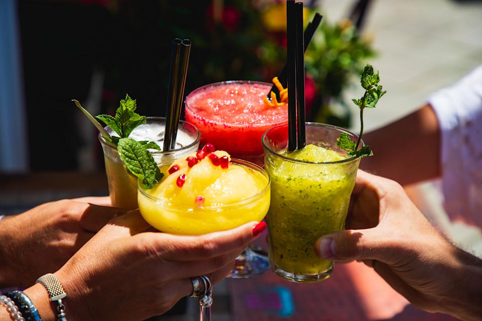 Four hands holding drinking glasses with yellow and red fruit cocktails, proposing a toast at outdoor party