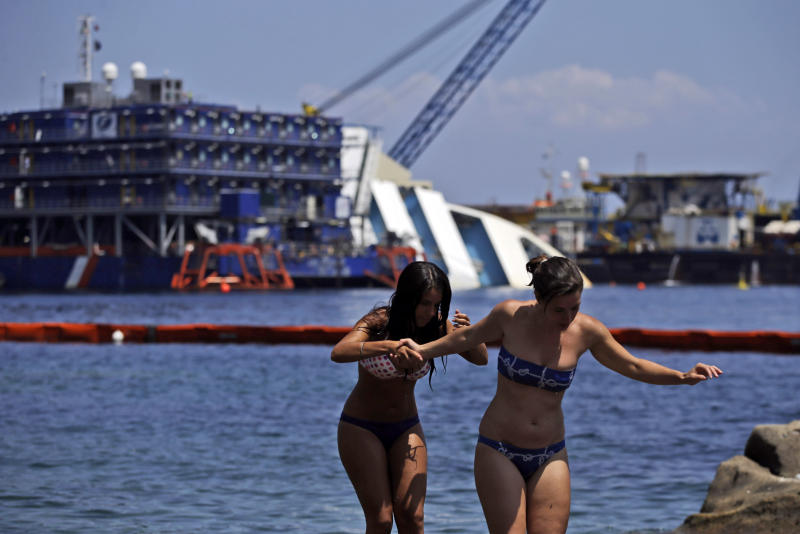 Sunbathers walk on rocks as the Costa Concordia cruiser is visible in background, in the Tuscan Island of Isola del Giglio, Monday, July 15, 2013. Salvage crews are working against time to right and remove the shipwrecked Costa Concordia cruise ship, which is steadily compressing down on itself from sheer weight onto its granite seabed perch off the Tuscan island of Giglio. Salvage master Nick Sloane said Monday that the Concordia has compressed some 3 meters (10 feet) since it came to rest on the rocks Jan. 13, 2012 after ramming a jagged reef during a stunt ordered by the captain that cost the lives of 32 people. (AP Photo/Gregorio Borgia)
