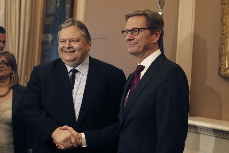 Greece's Foreign Minister Evangelos Venizelos, left, shakes hands with his German counterpart Guido Westerwelle, during their meeting in Athens, on Wednesday, July 3, 2013. Westerwelle is in Greece on a two-day official visit. (AP Photo/Petros Giannakouris)