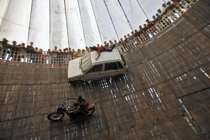 """Stunt performers ride a bike and a car on the walls of the """"Well of Death"""", one of the attractions at Ramlila fair, in the old quarters of Delhi. The performers earn their livelihood by performing daredevil stunts such as driving their bikes and cars on the walls of the """"Well of Death"""" attraction, which draws a large number of spectators. (REUTERS/Adnan Abidi)"""