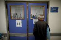 A man watches his wife who is suspected of having COVID-19 as she is attended at Llavallol Dr. Norberto Raúl Piacentini Hospital in Lomas de Zamora, Argentina, Saturday, May 1, 2021. The man's wife was intubated and a few days later passed away. (AP Photo/Natacha Pisarenko)