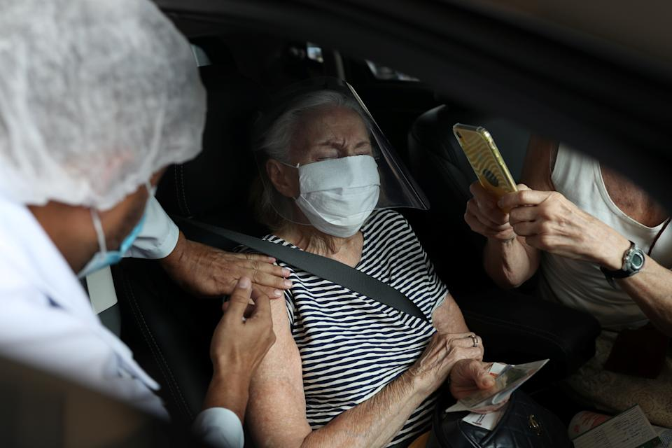 A woman receives a dose of the coronavirus disease (COVID-19) vaccine at a drive-thru vaccination station for people aged 90 years or older at Pacaembu stadium in Sao Paulo, Brazil February 8, 2021. REUTERS/Amanda Perobelli