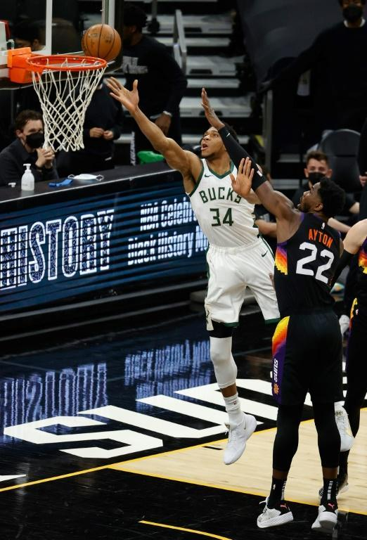 Milwaukee's Giannis Antetokounmpo shoots a layup against Phoenix, but his status for Tuesday's NBA Finals opener against the Suns is questionable due to a left knee injury