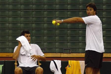 Australia's Davis Cup tennis team captain Pat Rafter (R) talks with player Bernard Tomic (L) during a practice session at the Beijing International Tennis Centre July 5, 2011. REUTERS/David Gray