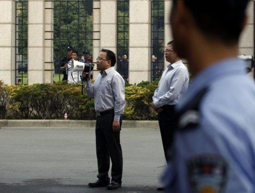 <p>A Chinese government official tries to calm protesters as they march down the street in Ningbo, east China's Zhejiang province on Sunday.</p>