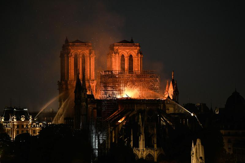 Firefighters douse flames burning the roof of the Notre Dame Cathedral in Paris on April 15, 2019.