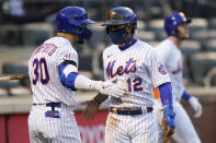 New York Mets' Francisco Lindor (12) celebrates with Michael Conforto (30) after scoring on a single by Pete Alonso during the eighth inning of a baseball game against the Philadelphia Phillies as Jeff McNeil (6) walks away in the first game of a doubleheader Tuesday, April 13, 2021, in New York. The Mets won 4-3. (AP Photo/Frank Franklin II)