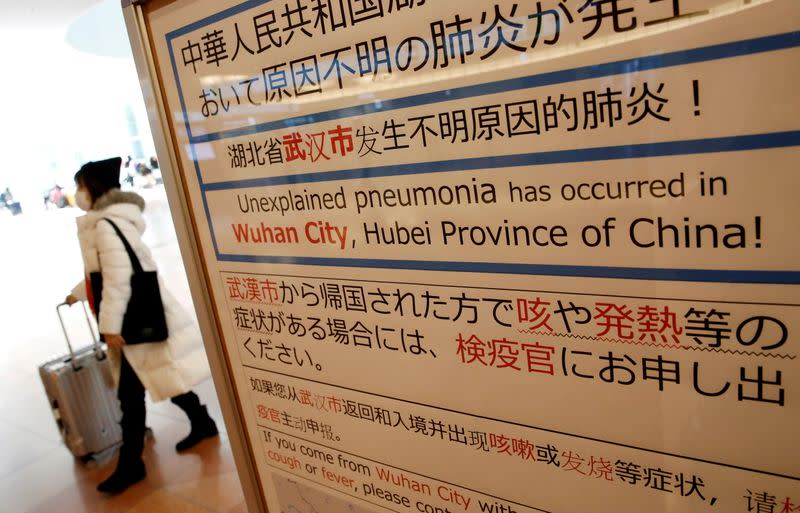 FILE PHOTO: A woman wearing a mask walks past a quarantine notice about the outbreak of coronavirus in Wuhan, China at an arrival hall of Haneda airport in Tokyo