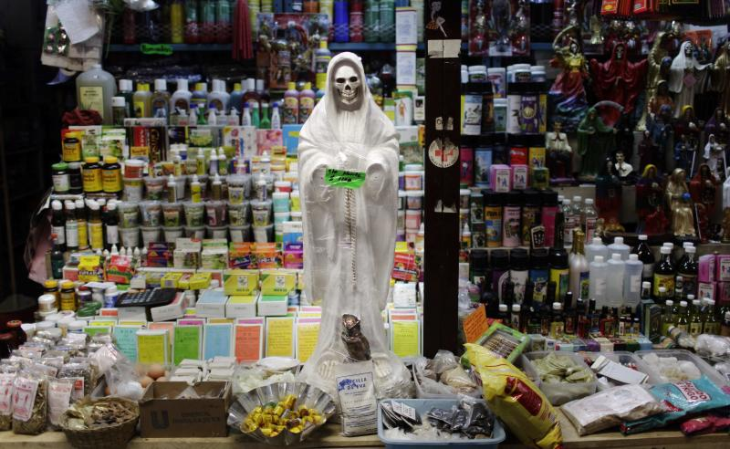 "FILE - In this April 9, 2009 file photo, a skeletal figure representing the folk saint known in Mexico as ""Santa Muerte"" or ""Death Saint,"" sits in a vendor's stall at a market in Ciudad Juarez, Mexico. Eight people have been arrested for allegedly killing two boys and a woman in ritual sacrifices by the cult of La Santa Muerte, or Saint Death, according to prosecutors in northern Mexico on Friday March 30, 2012. Jose Larrinaga, spokesman for Sonora state prosecutors, said the first of the three victims was apparently killed in 2009, the second in 2010 and the latest in March 2012. (AP Photo/Rodrigo Abd, File)"