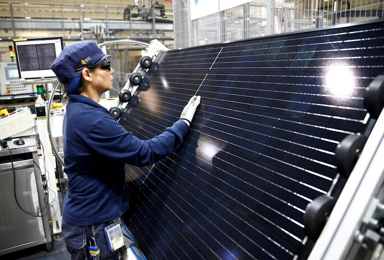 FILE PHOTO: An employee makes a final inspection on panels during a tour of an REC solar panel manufacturing plant in Singapore, May 5, 2017. Picture taken May 5, 2017.  REUTERS/Edgar Su/File Photo