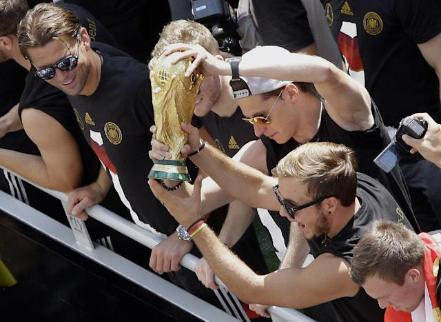"German soccer players Mario Goetze, right, and Julian Draxler , center, hold the trophy while goalie Roman Weidenfeller , left, looks on, after the arrival of the German national soccer squad in Berlin Tuesday, July 15, 2014. Germany's World Cup-winning team has returned home from Brazil to celebrate the country's fourth title with huge crowds of fans. The team's Boeing 747 touched down at Berlin's Tegel airport midmorning Tuesday after flying a lap of honor over the ""fan mile"" in front of the landmark Brandenburg Gate. (AP Photo/Michael Sohn)"