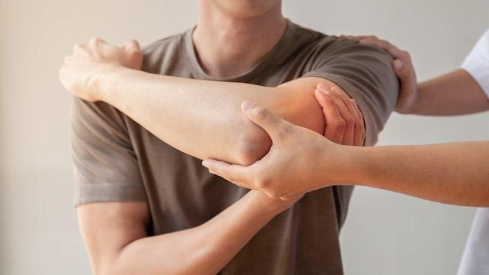 A medical professional checking a man's elbow