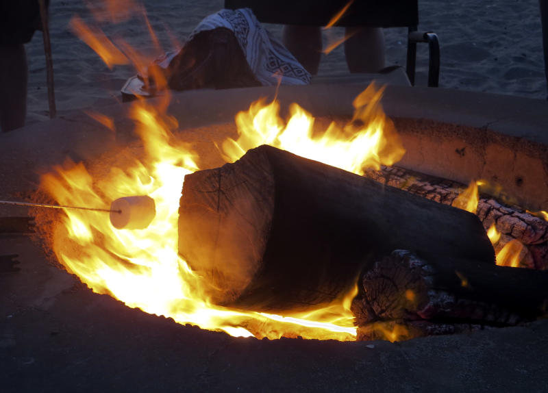 A marshmallow gets toasted around a fire pit at Bolsa Chica State Beach Saturday, April 27, 2013 in Huntington Beach, Calif. Air quality regulators are considering a proposal to ban beach bonfires in Southern California due to health concerns. (AP Photo/Chris Carlson)