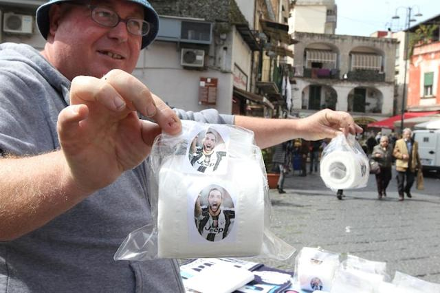A vendor shows toilet paper rolls with portraits of Juventus' Argentinian forward Gonzalo Higuain on March 23, 2017 in a street of Naples (AFP Photo/CARLO HERMANN)
