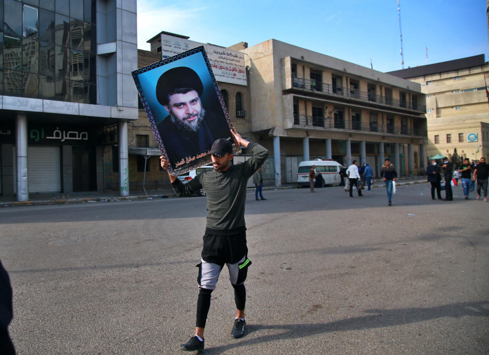 Followers of Shiite cleric Muqtada al-Sadr, in the poster, head to Tahrir Square, Baghdad, Iraq, Friday, Nov. 27, 2020. Thousands took to the streets in Baghdad on Friday in a show of support for a radical Iraqi cleric ahead of elections slated for next year, stirring fears of a spike in coronavirus cases. (AP Photo/Khalid Mohammed)