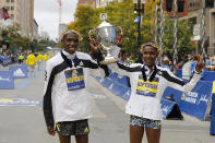 Benson Kipruto, left, and Diana Kipyogei, both of Kenya, celebrate winning the men's and women's divisions of the 125th Boston Marathon on Monday, Oct. 11, 2021, in Boston. (AP Photo/Winslow Townson)