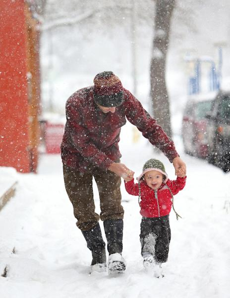 Julian Tucci, 1, enjoys his first snowfall with father Jeremy Tucci along Willamette Street in Eugene, Ore. on Friday, Dec. 6, 2013.(AP Photo/The Register-Guard, Brian Davies)