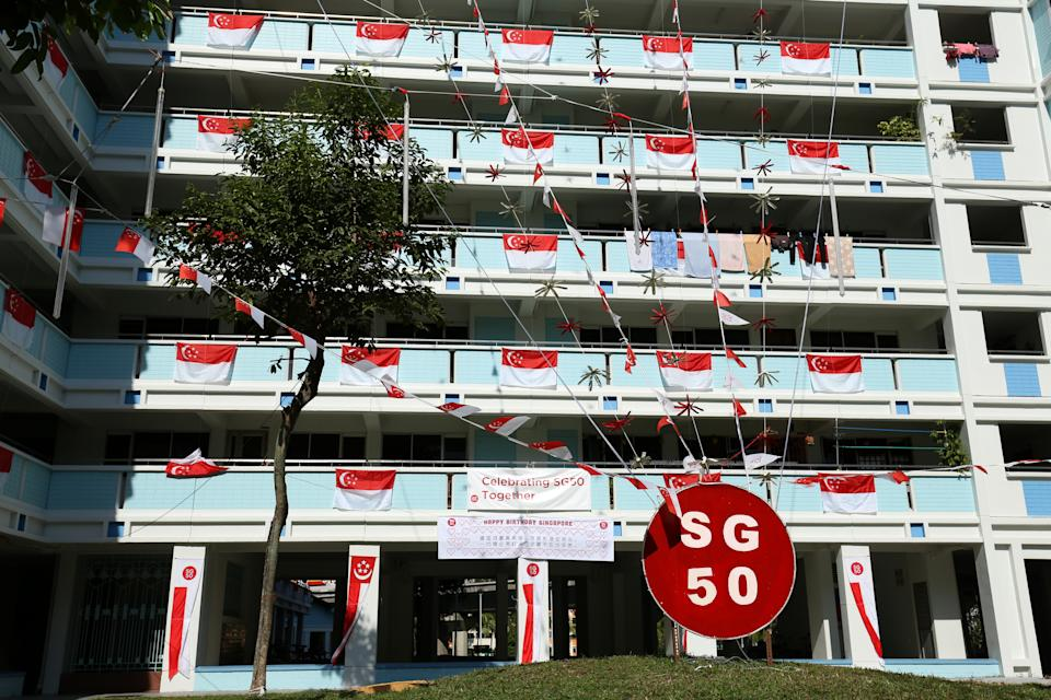 SINGAPORE - JULY 22:  Rows of Singapore national flags and SG50 decorations are put up on an apartment block on July 22, 2015 in Singapore. Singapore will be celebrating her fiftieth birthday on August 9, 2015.  (Photo by Lionel Ng/Getty Images)