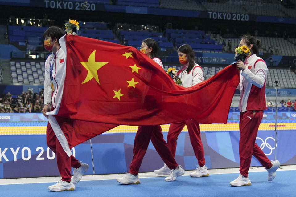 China's women's 4x200-meter freestyle relay team, of Yang Junxuan, Tang Muhan, Zhang Yifan and Li Bingjie carry their national flag after receiving their gold medals at the 2020 Summer Olympics, Thursday, July 29, 2021, in Tokyo, Japan. (AP Photo/Matthias Schrader)