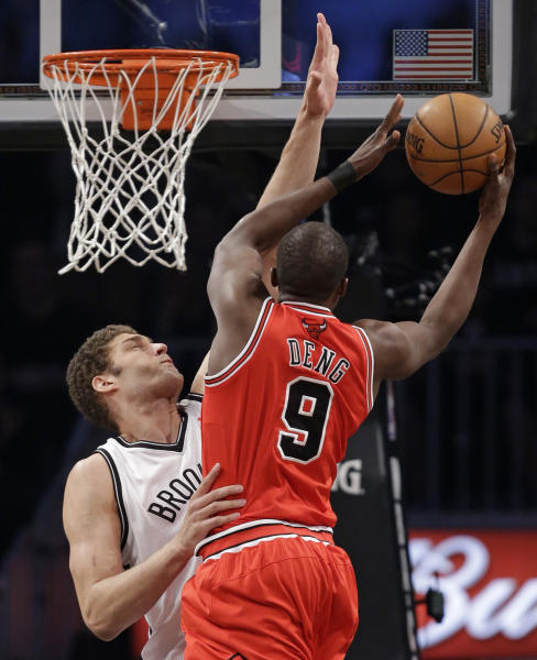 Brooklyn Nets center Brook Lopez (11) defends as Chicago Bulls forward Luol Deng (9) goes up for a layup in the first half of Game 2 of their first-round NBA basketball playoff series, Monday, April 22, 2013, in New York. (AP Photo/Kathy Willens)