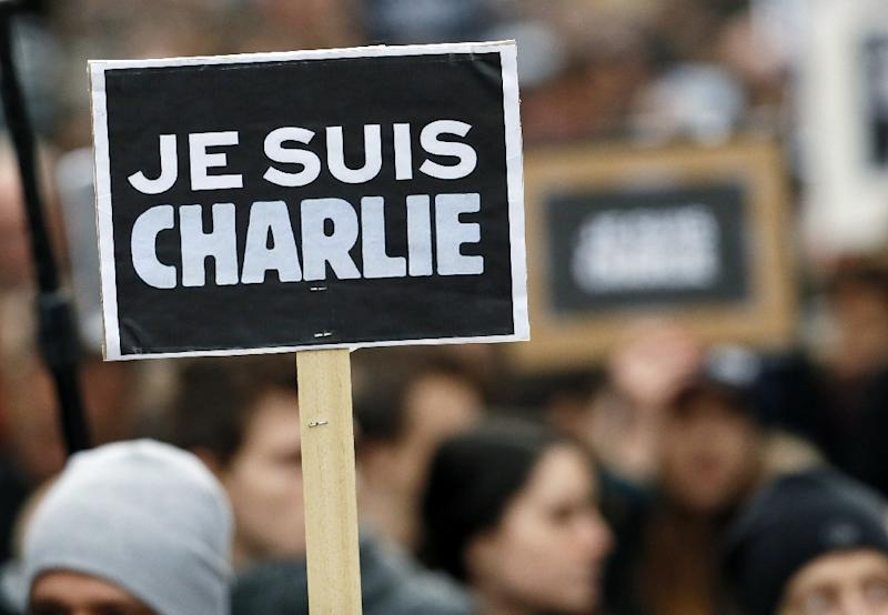 """People hold posters reading """"I am Charlie"""" during rally in Paris on January 11, 2015 in tribute to the victims of the Charlie Hebdo attacks"""